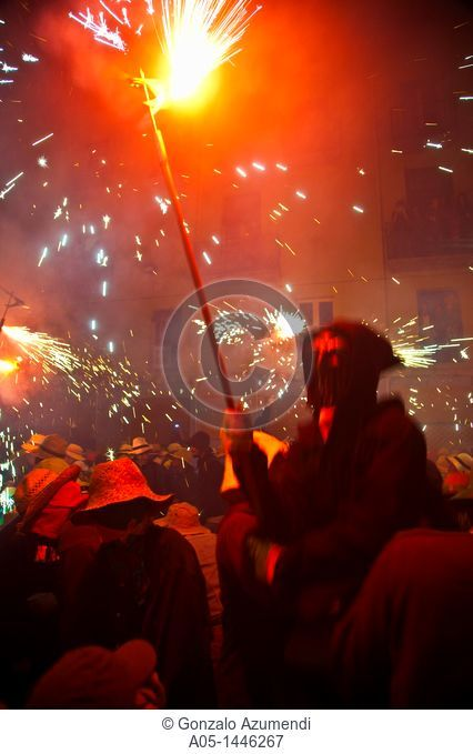 'Correfoc' Catalan traditional festival 16th August where people dressed as devils light fireworks while dancing in the street, La Bisbal d'Emporda