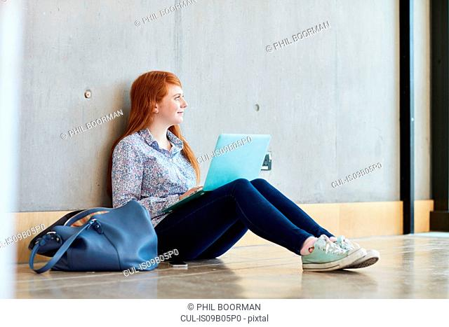 Young female student sitting on floor with laptop at higher education college