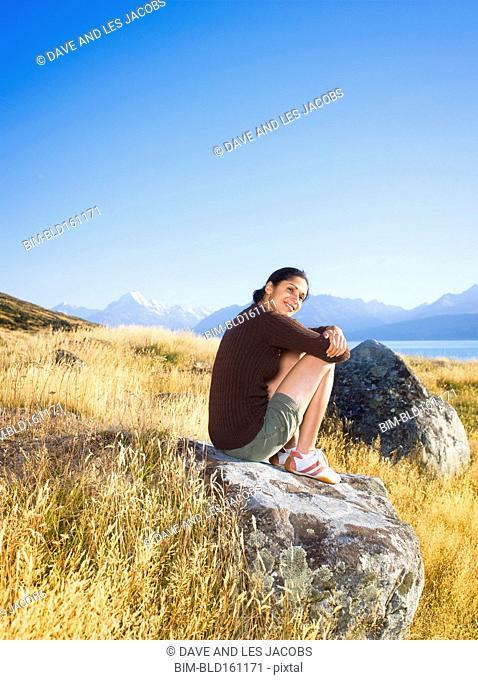 Hispanic hiker sitting on rock formation in remote field