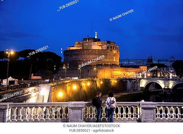 Couple of tourist watching Castel Sant'Angelo from bridge at night, Rome, Italy, Europe