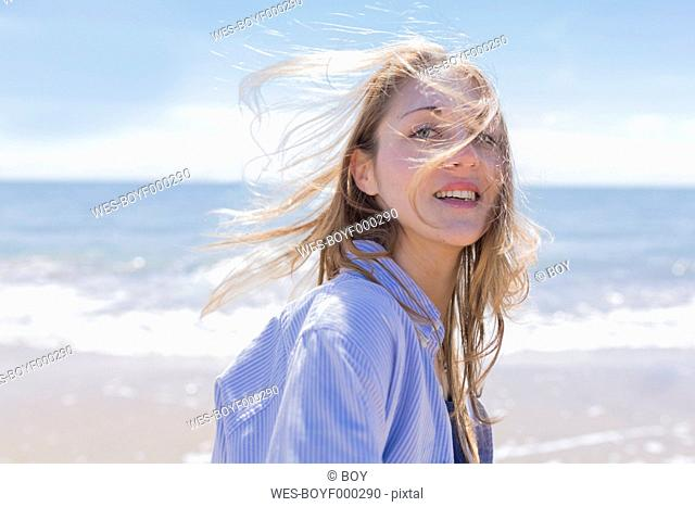Portrait of smiling young woman with blowing hair at seaside