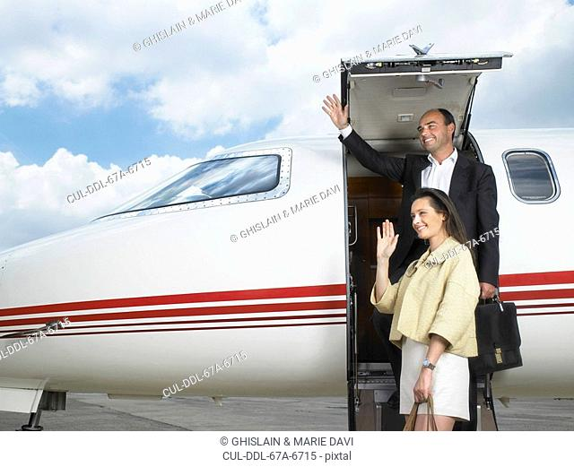 Couple exiting private jet while waving
