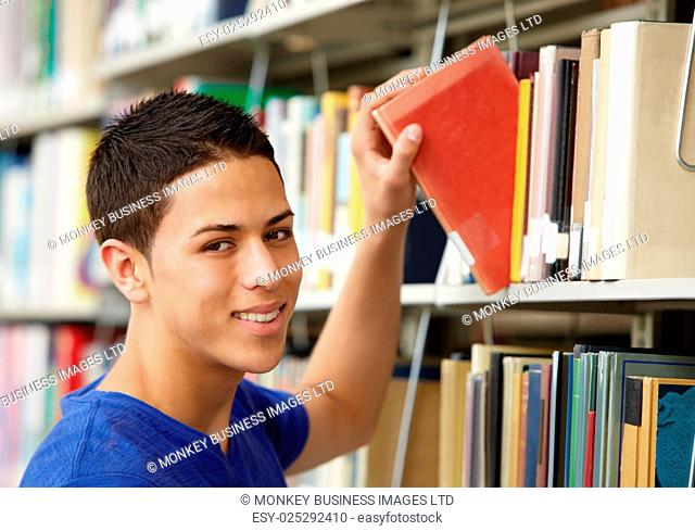 Teenage boy working in library