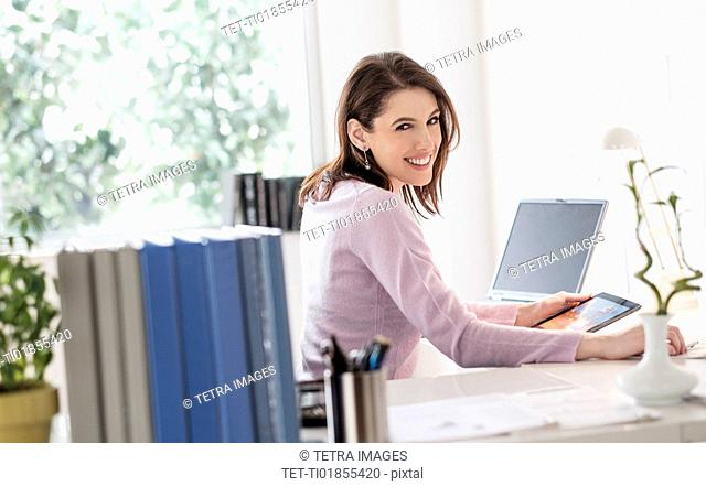Young woman using digital tablet, looking at camera