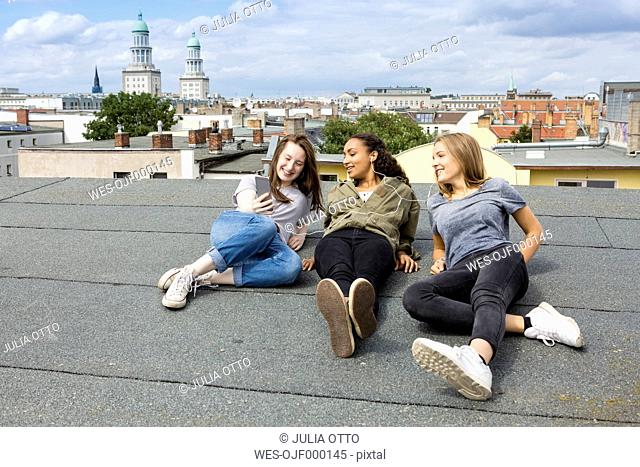 Germany, Berlin, three teenage girls sitting on roof top listening music with earphones
