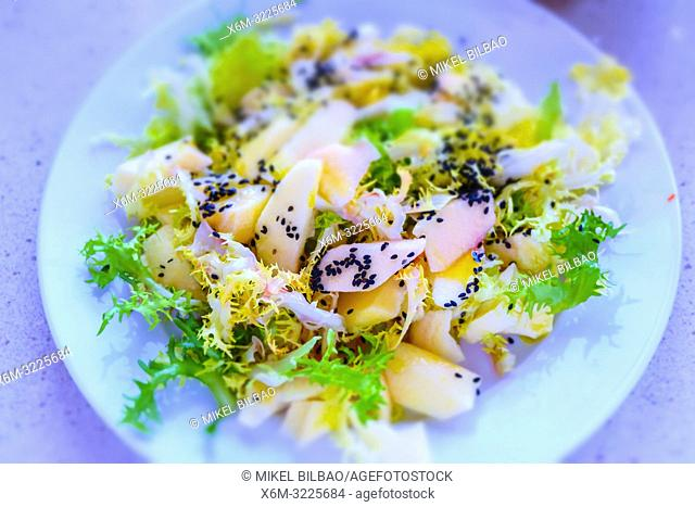 Escarole salad with apple and black sesame seeds with umeboshi vinegar. Macrobiotic recipe