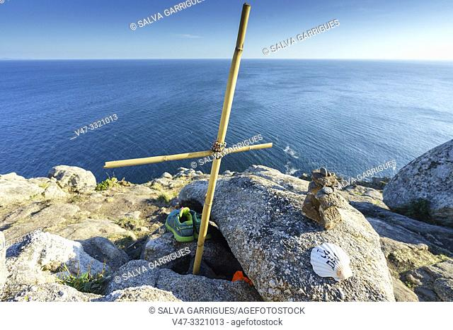Improvised crosses and scallops of pilgrims mark the end of the road at Cape Finisterre, A Coruña, Galicia, Spain
