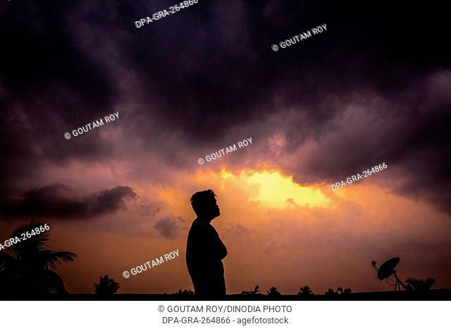 Man looking at monsoon clouds, Barasat, Kolkata, West Bengal, India, Asia