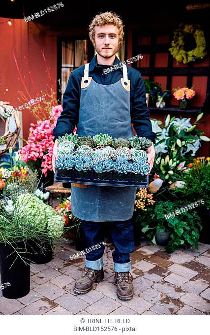 Caucasian florist carrying tray of succulents outside shop