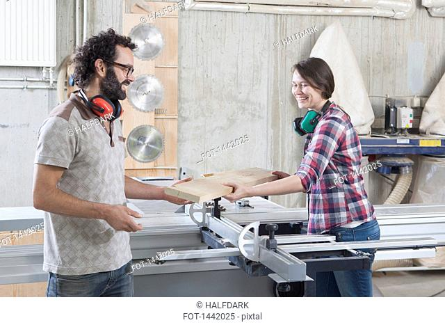 Carpenters laughing while using sliding table saw in workshop