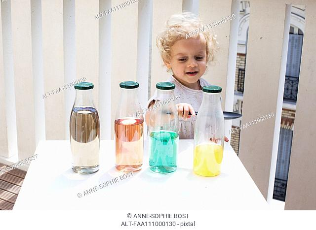 Little girl making sounds tapping bottles of water