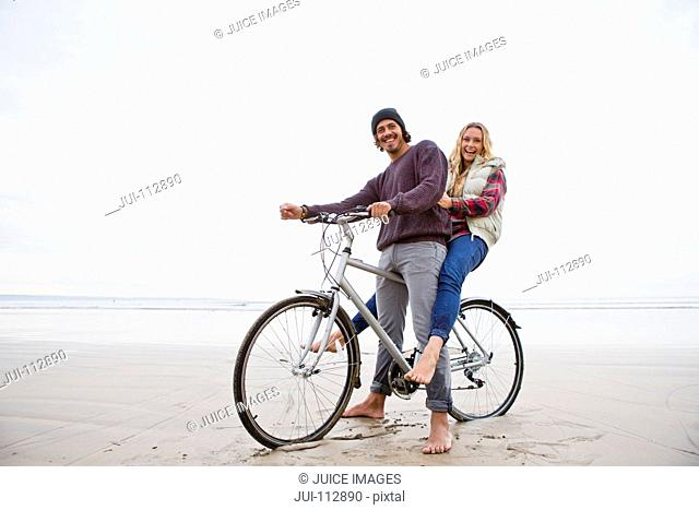 Portrait smiling couple sharing bicycle on beach