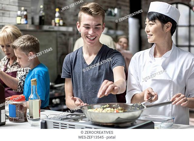 Teenager and female chef cooking together