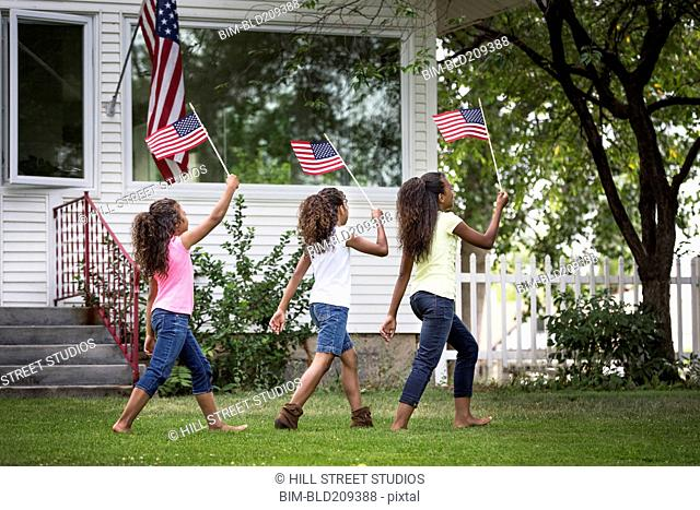 Mixed race girls marching with American flags