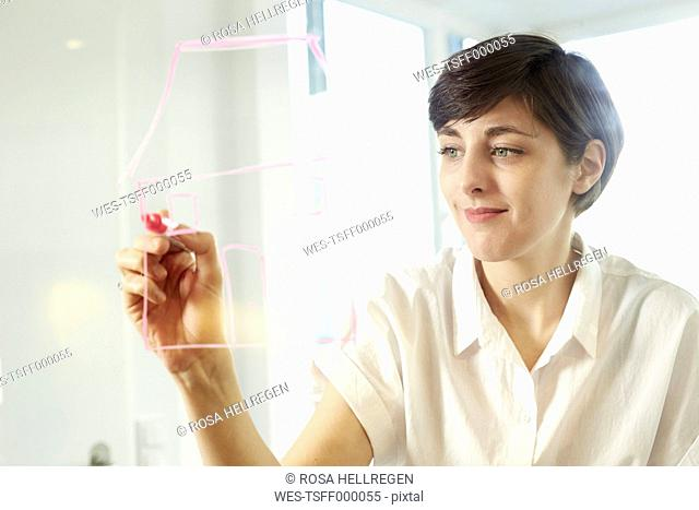 Portrait of woman drawing a house on glass pane in an office
