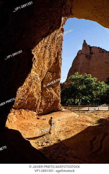A woman looks inside Galerias de la Cuevona. Guided visit to the remains of the Roman mining of Las Médulas. Trail of the Valiñas
