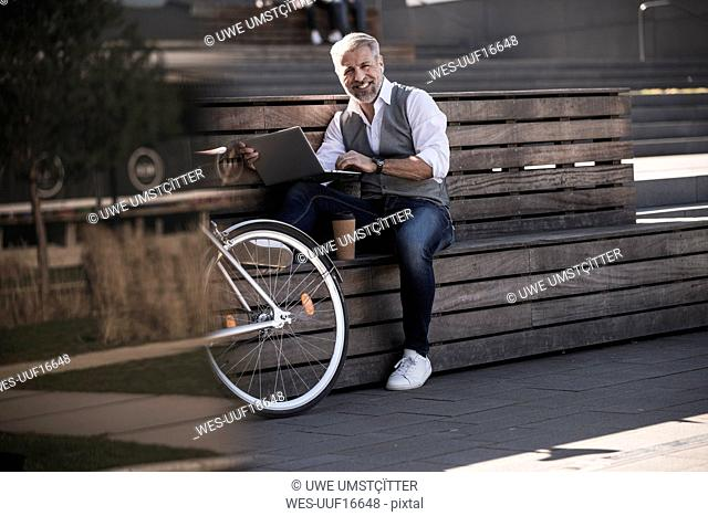 Smiling mature businessman with bicycle sitting on a bench using laptop