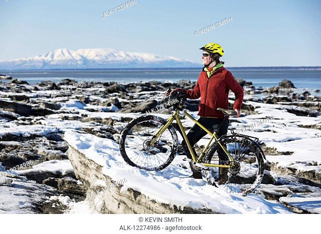 Young woman with her bicycle stands on frozen ice chunks along the Tony Knowles Coastal Trail, Anchorage, Southcentral Alaska