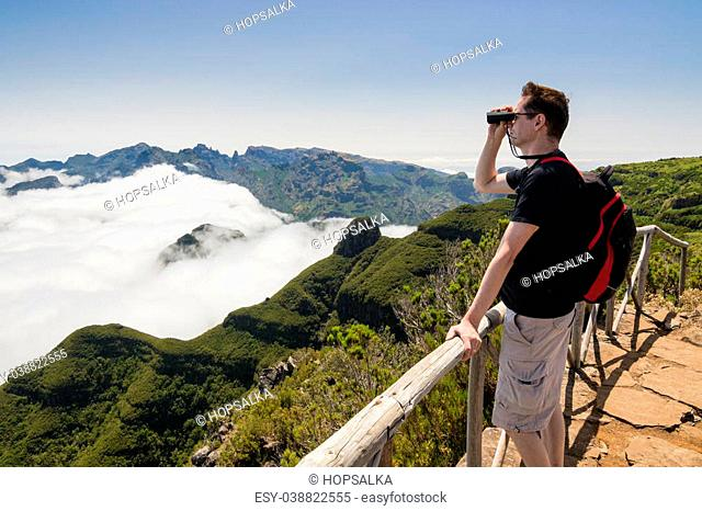 A man standing on a viewpoint above clouds, looking into binoculars and admiring a spectacular view from Paul da Serra plateau over Pico Ruivo mountain