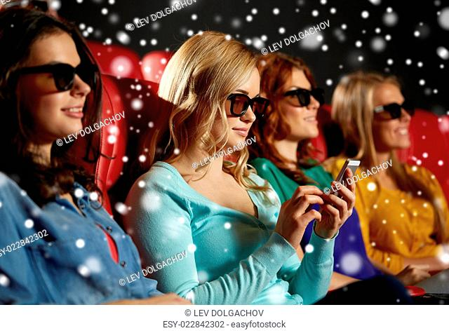 cinema, technology, entertainment and people concept - happy woman in 3d glasses reading message on smartphone in movie theater with friends over snowflakes