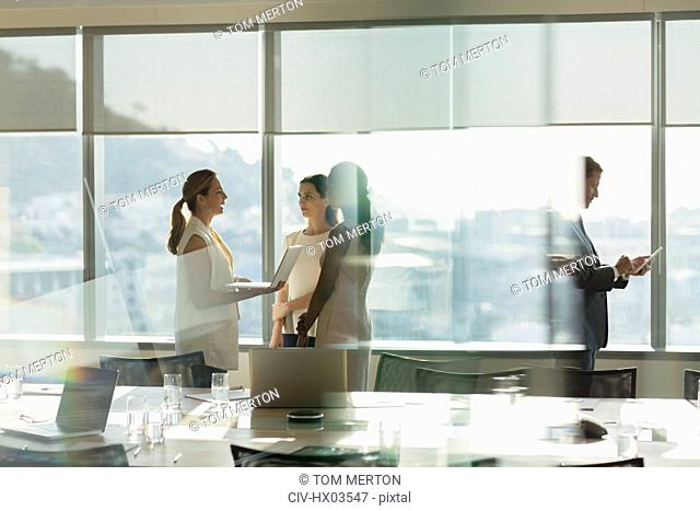 Businesswomen talking, using laptop in sunny conference room meeting
