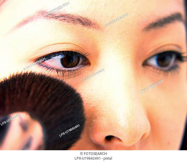 Young Woman Applying Face Powder, Close Up, Differential Focus