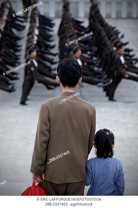 Father And Daughter Watching North Korean Army Parade In Pyongyang, North Korea