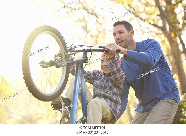 Father teaching son wheelie on bicycle