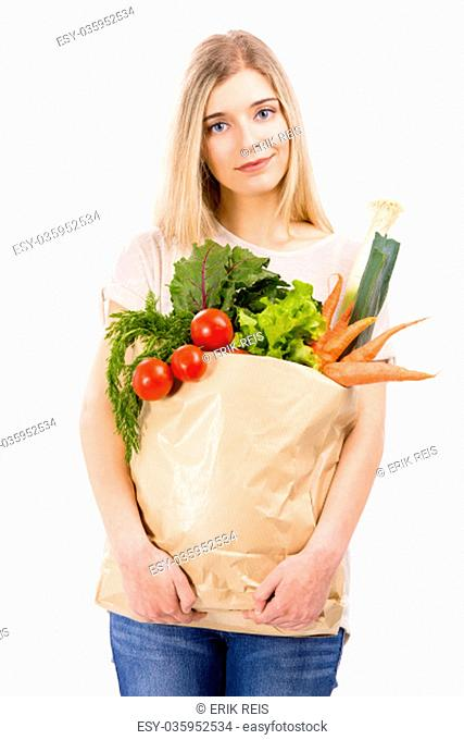 Beautiful blonde woman carrying a bag full of vegetables with thumbs up, isolated over white background