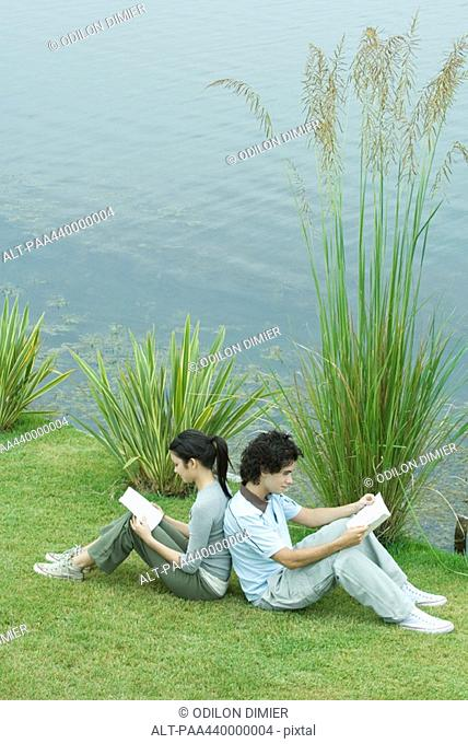 Young adult couple reading outdoors, sitting back to back on grass by edge of lake