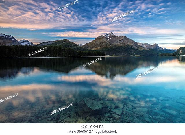 Pink sky at dawn illuminates the peaks reflected in Lake Sils Engadine Canton of Graubünden Switzerland Europe