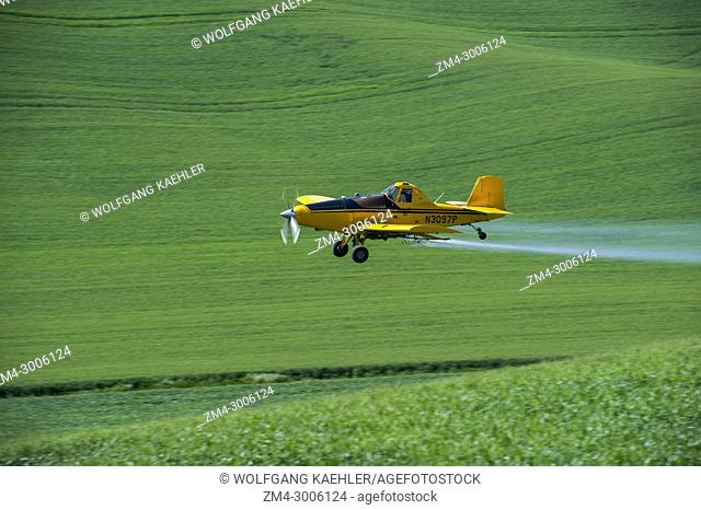 Crop duster plane flying over field near Pullman in the Palouse, Eastern Washington State, USA