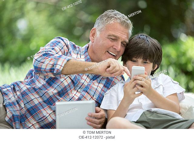 Grandfather and grandson using digital tablet and cell phone