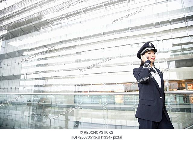 Female pilot talking on a mobile phone
