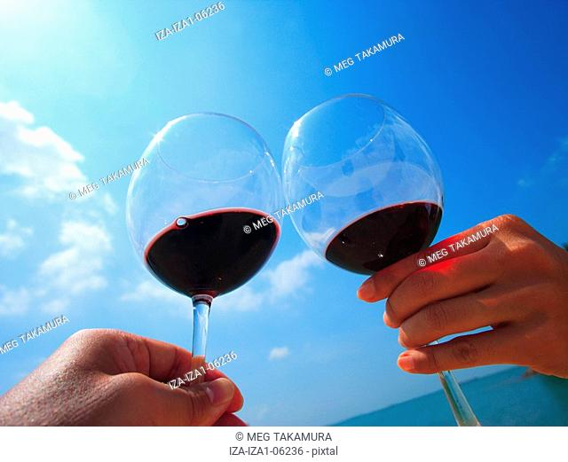Low angle view of two hands toasting with wine glasses