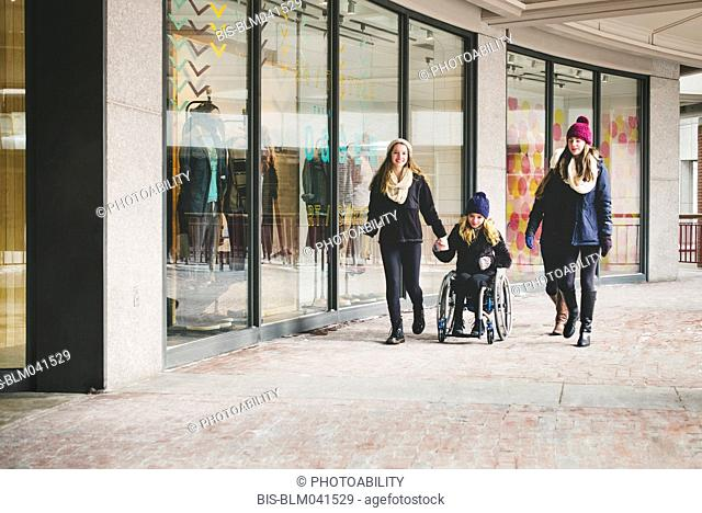 Girls walking and using wheelchair near retail store