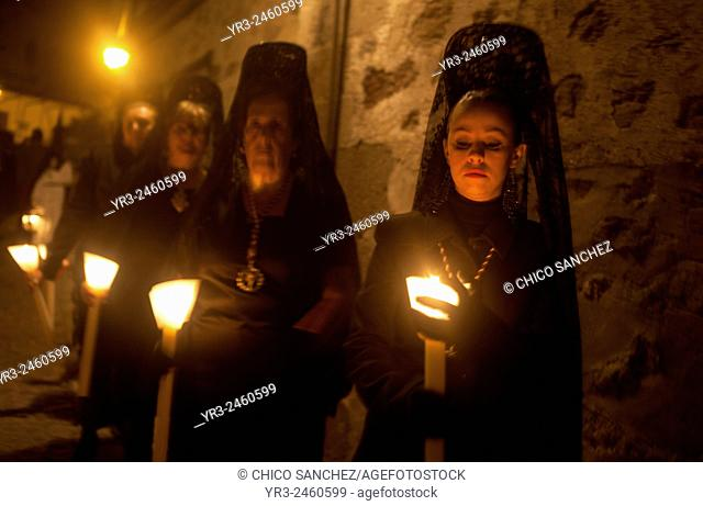 Women wearing mantillas hold candles during an Easter Holy Week procession in Trujillo, Extremadura, Spain