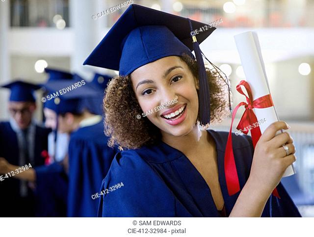 Portrait smiling female college graduate in cap and gown holding diploma