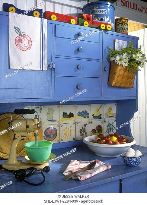 KITCHEN - Vacation home. Blue painted Hoosier style cupboard, antiques, vintage mixer with jadite bowl, wooden toys, old tins, colorful, bowl of strawberries