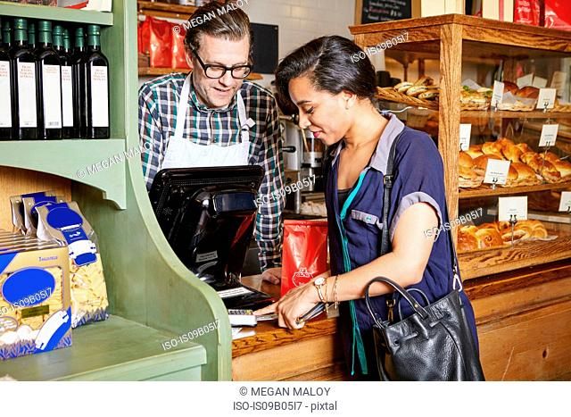 Customer in bakery paying for goods, using card machine