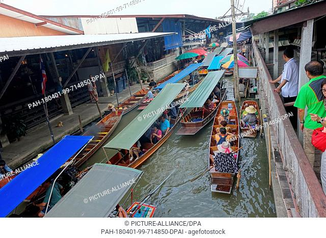 26 February 2018, Damnoen Saduak, Thailand: Boats with hawkers, tourists and locals floating along a canal in the floating market of Damnoen Saduak