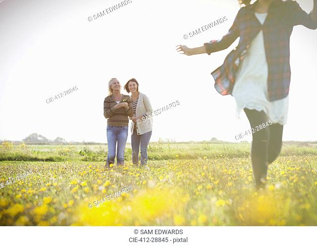 Women watching girl run in sunny meadow with wildflowers