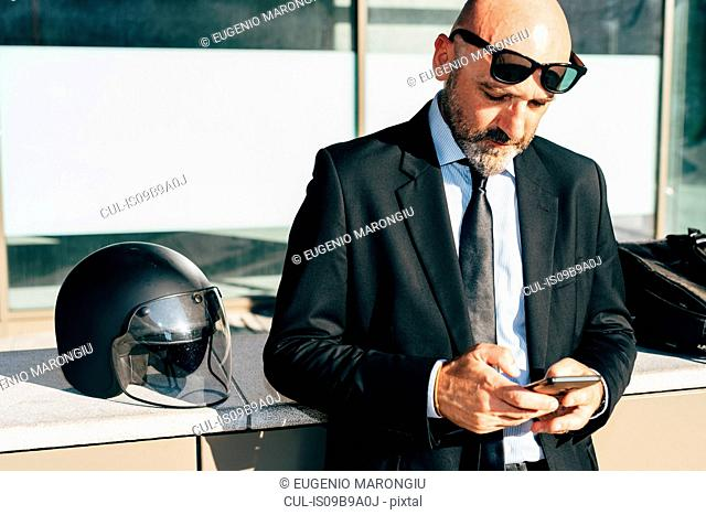 Mature businessman standing outdoors, using smartphone, motorcycle helmet on wall beside him