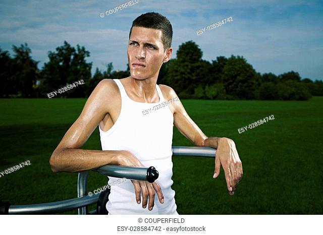 Very slim and tall man exercising on outdoor location on public park fitness in summer time