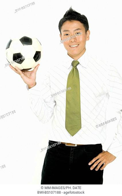 A young businessman with a football in his hand
