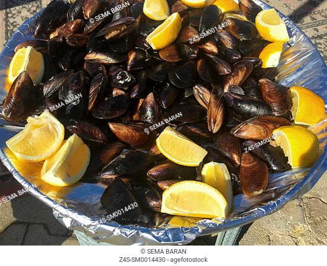 Tray full of mussels with lemons at the street market of the Sigacik town, Seferihisar, Izmir, Aegean Coast, Turkey, Europe