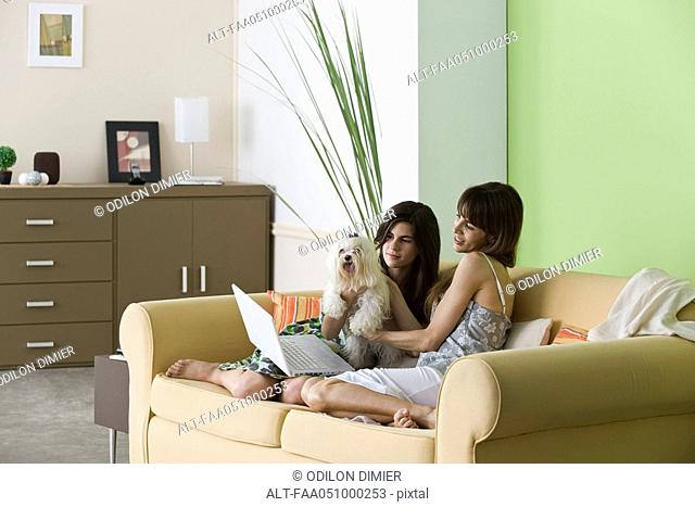 Woman relaxing with pet dog and teenage daughter