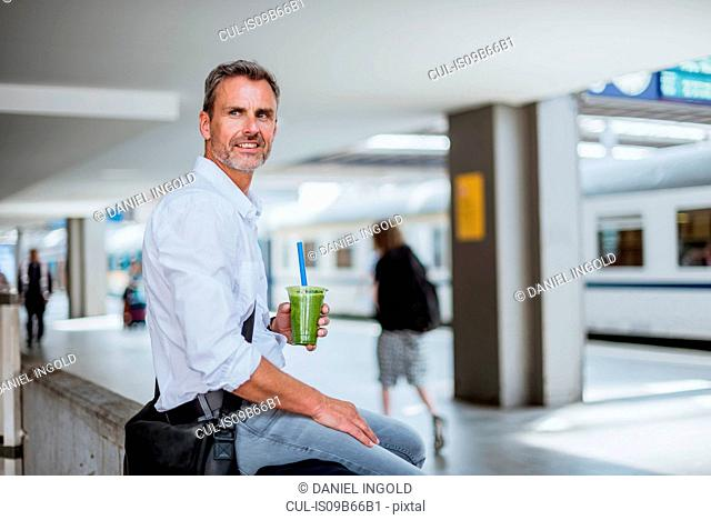 Mature man sitting on wall at station platform, waiting for train, holding healthy juice drink