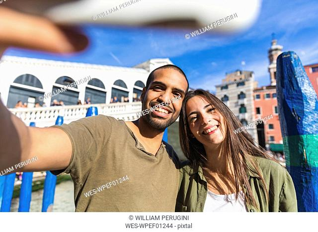 Italy, Venice, couple enjoying the city and taking a selfie with Rialto bridge in background