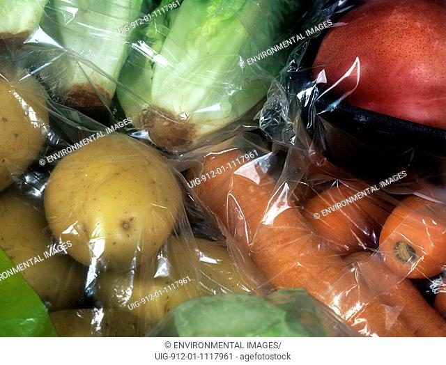 Unnecessary packaging - clear plastic bag & cellophane wrapping on veg sold in supermarket - potatoes, carrots & lettuce